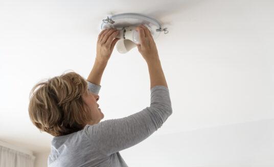 A senior woman performing senior home maintenance by changing a lightbulb