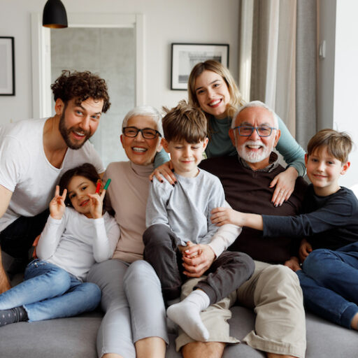 Seniors stay connected with friends and family in a big group photo with three kids, the adult parents and a senior man
