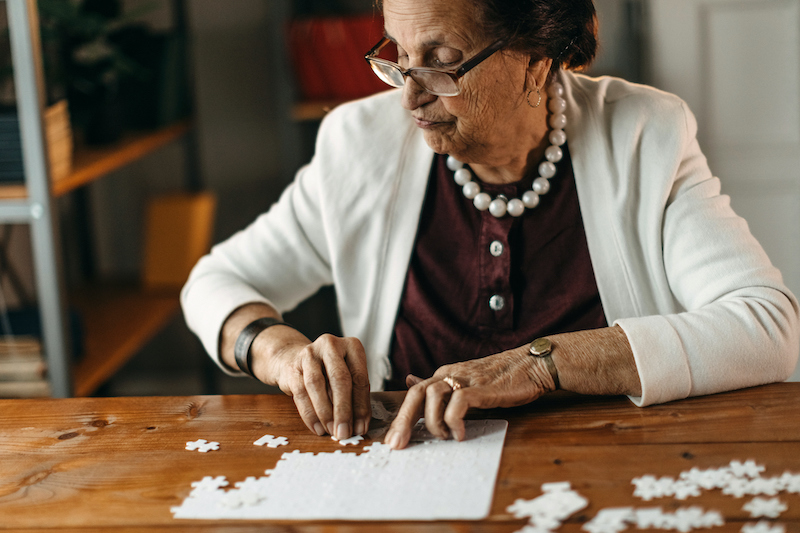 Senior woman putting together a puzzle on a wooden table, which is a great activity for seniors with dementia