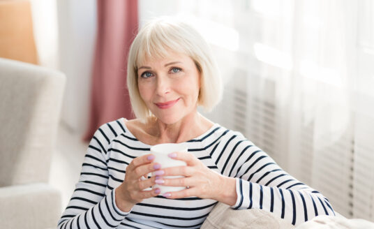 Senior woman drinks warm beverages on her living room couch to stay hydrated in autumn