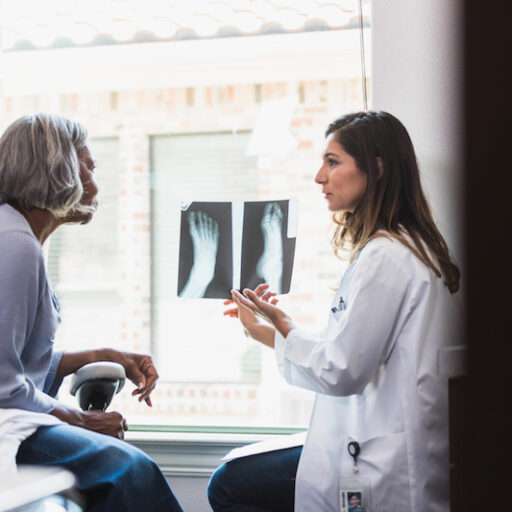 Female doctor assessing broken bones in seniors by xray as she consults the patient
