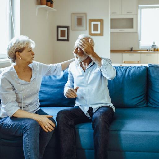 Senior woman and man sit on a couch, the woman tends to the man who is holding his head due to pain from a traumatic brain injury