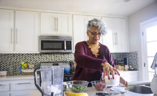 An older women preparing meal preps for senior caregivers in her kitchen