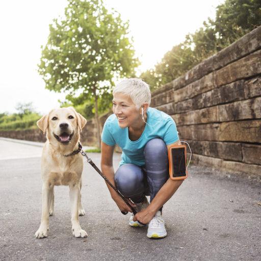 Senior woman walking her dog during fall to follow autumn exercise tips