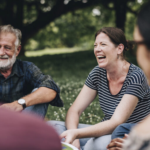Older adults reap the benefits of nostalgia by reminiscing together, seated in a circle outdoors during springtime.