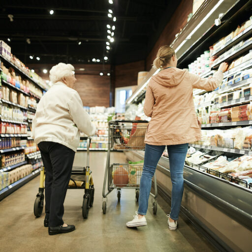 A young woman helps a senior woman with shopping at the grocery store