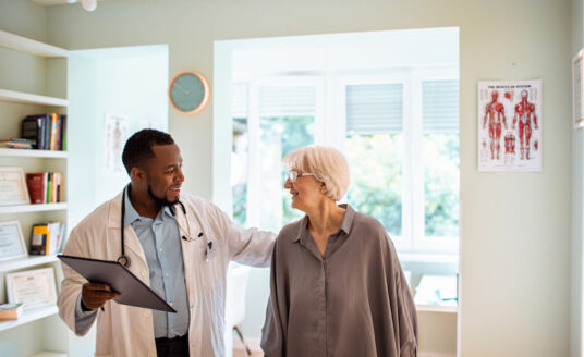 A senior woman receives preventive care for senior health issues by visiting and conversing with her male doctor in his office.