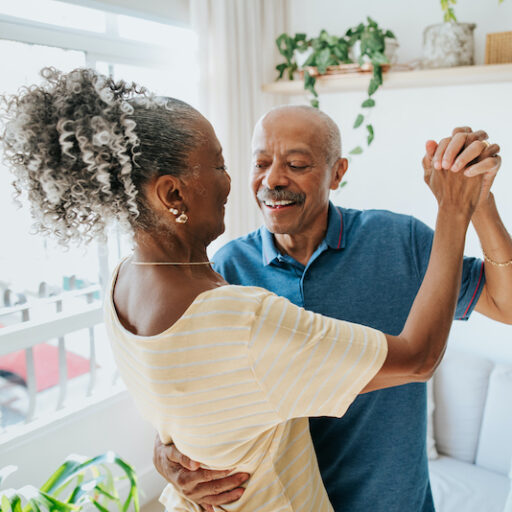 A senior man and woman enjoy the health benefits of dancing by dancing together in their home