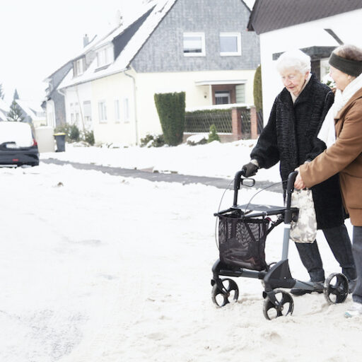 A senior woman with a walker practices fall prevention by traveling through the snow with a companion.
