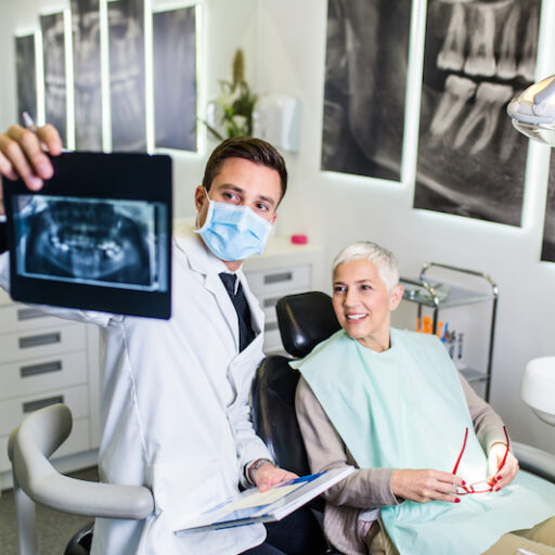 Senior man receives preventive dental care at his dentists office as he sits in the chair and looks at an xray